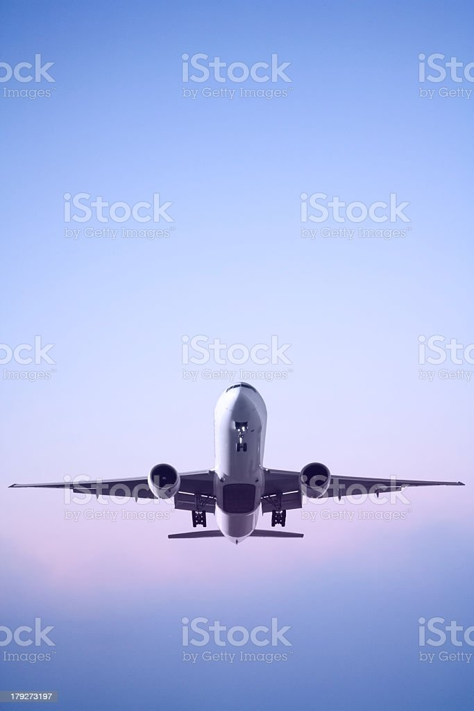 A jet airplane in landing sequence during dawn stock photo