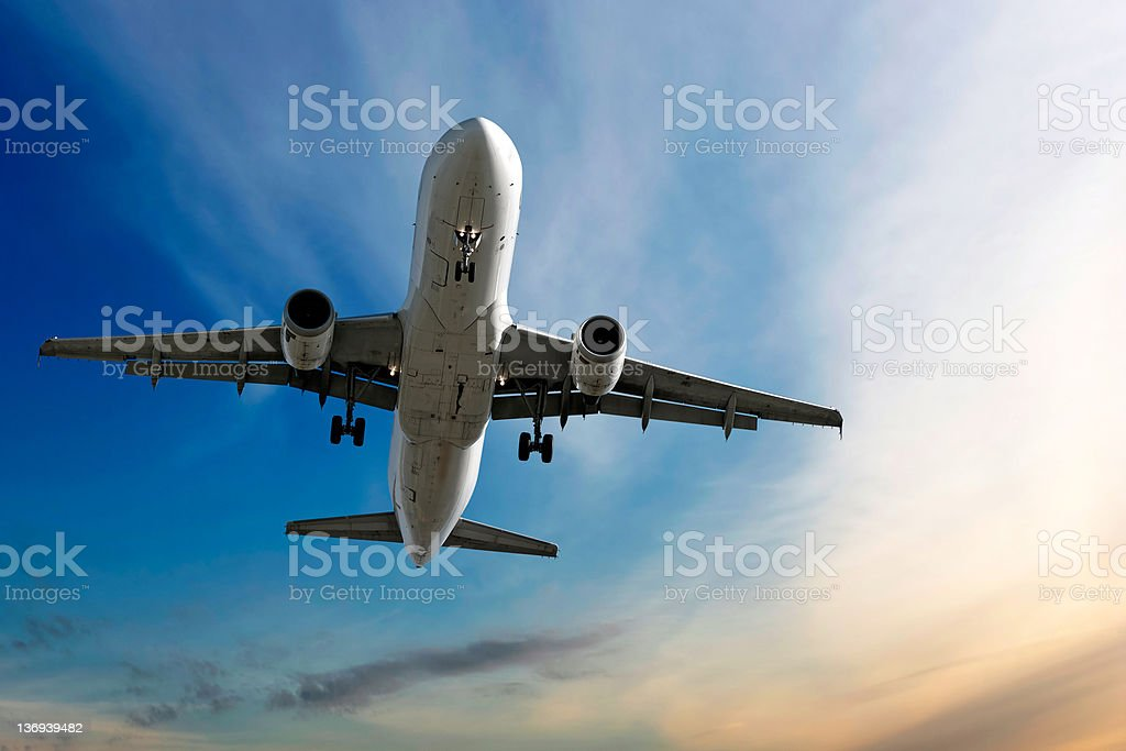 XL jet airplane landing at dusk stock photo