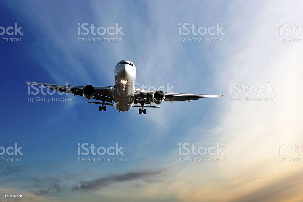 jet airplane landing at dusk stock photo