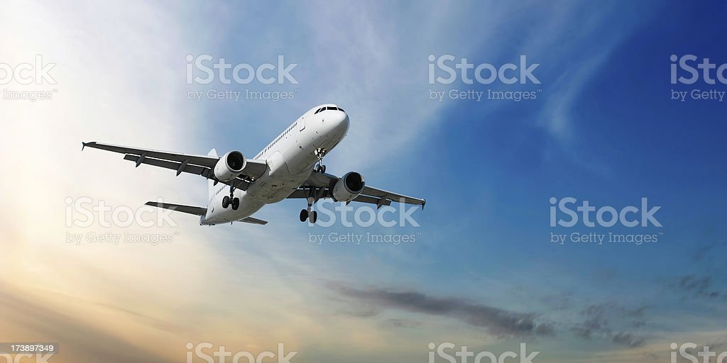 XXL jet airplane landing at dusk stock photo