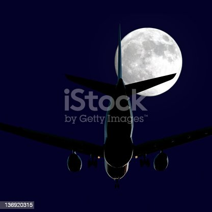 jet airplane in close-up landing at night with full moon, square frame