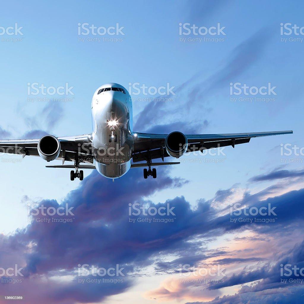 jet airplane landing at sunset royalty-free stock photo