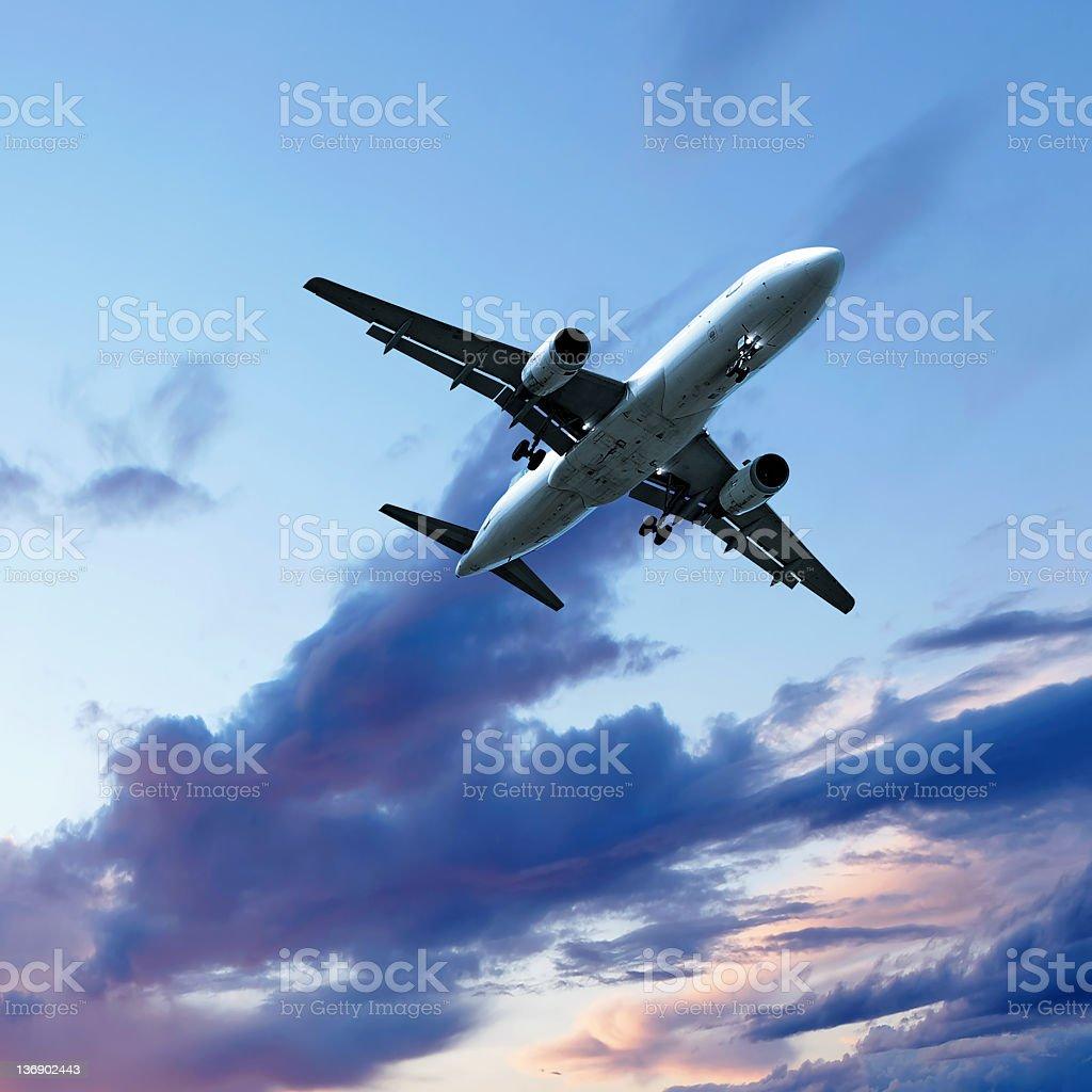 jet airplane landing at sunset stock photo