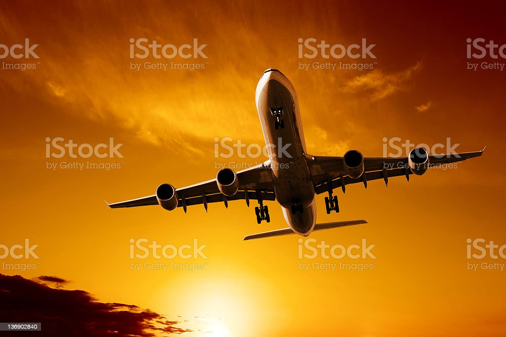 jet airplane landing at sunset royalty-free stock photo