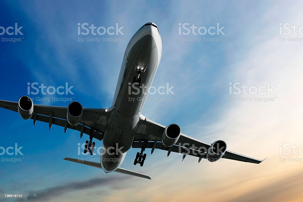 jet airplane landing at sunset stock photo