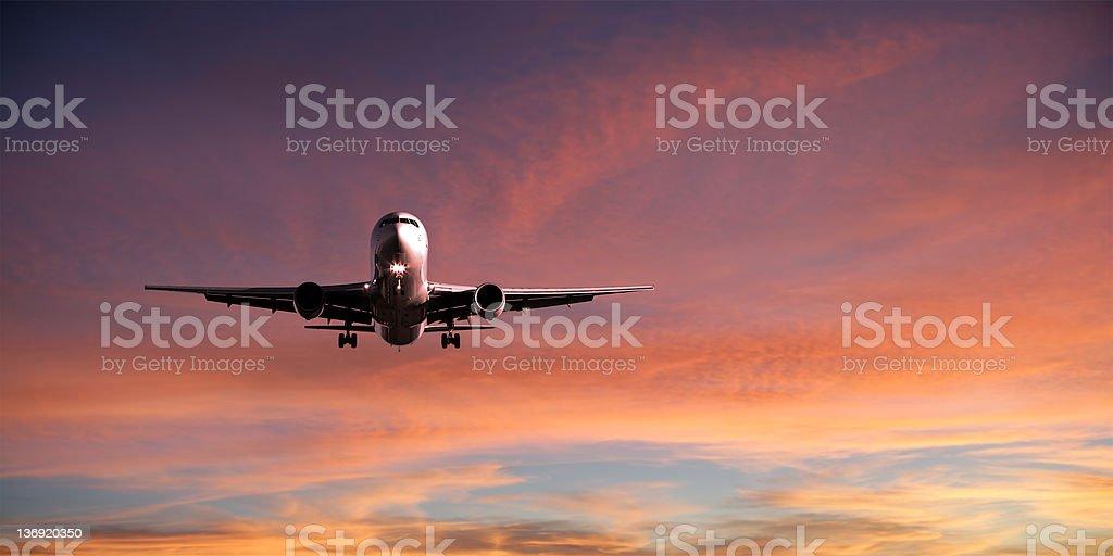 XXL jet airplane landing at sunset stock photo