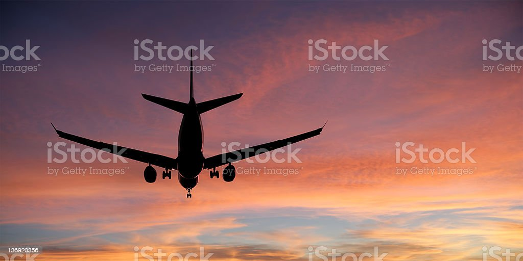 XXL jet airplane landing at sunset royalty-free stock photo