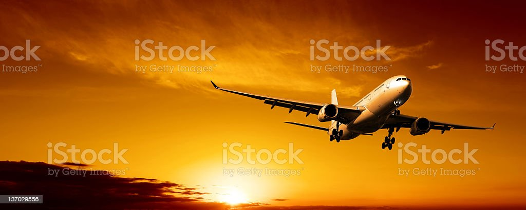 XL jet airplane landing at sunset stock photo