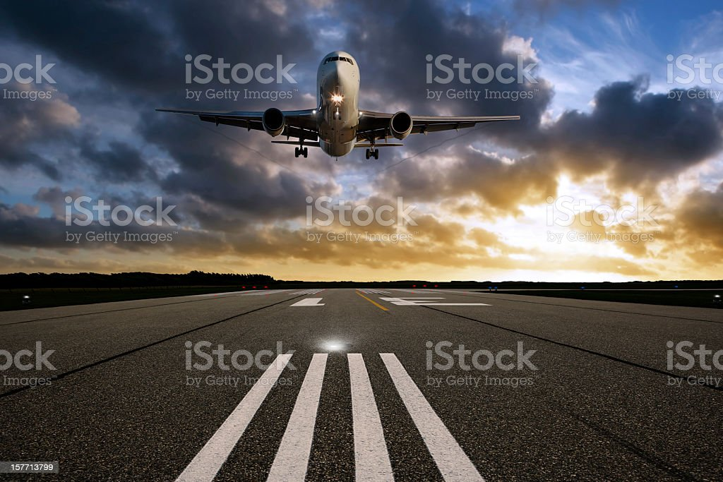 XXL jet airplane landing at sunset stock photo