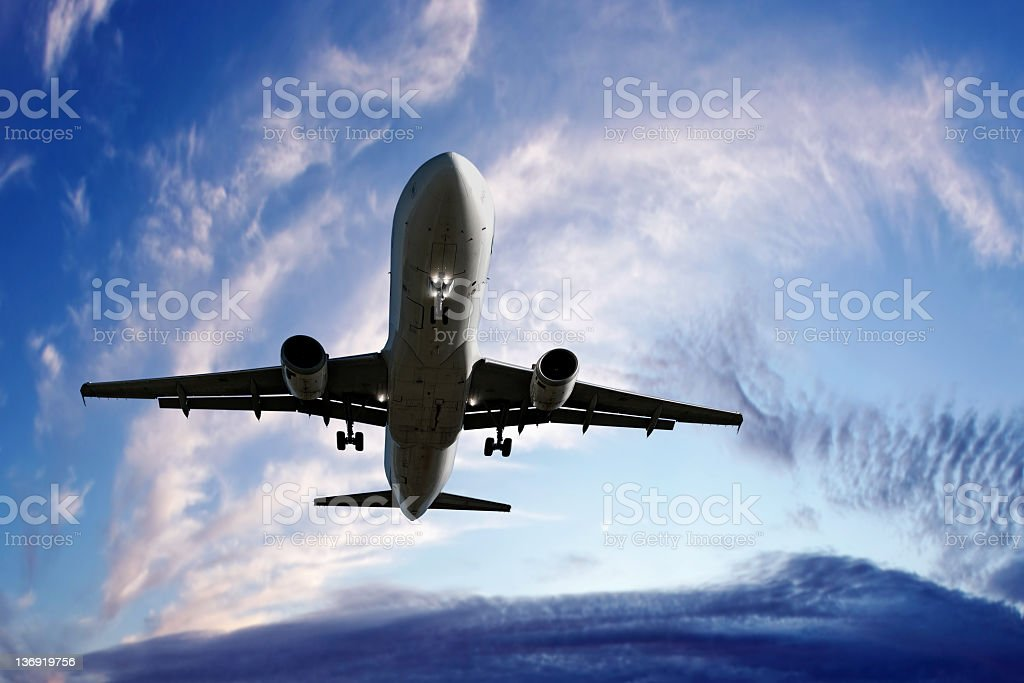 XL jet airplane landing at twilight stock photo
