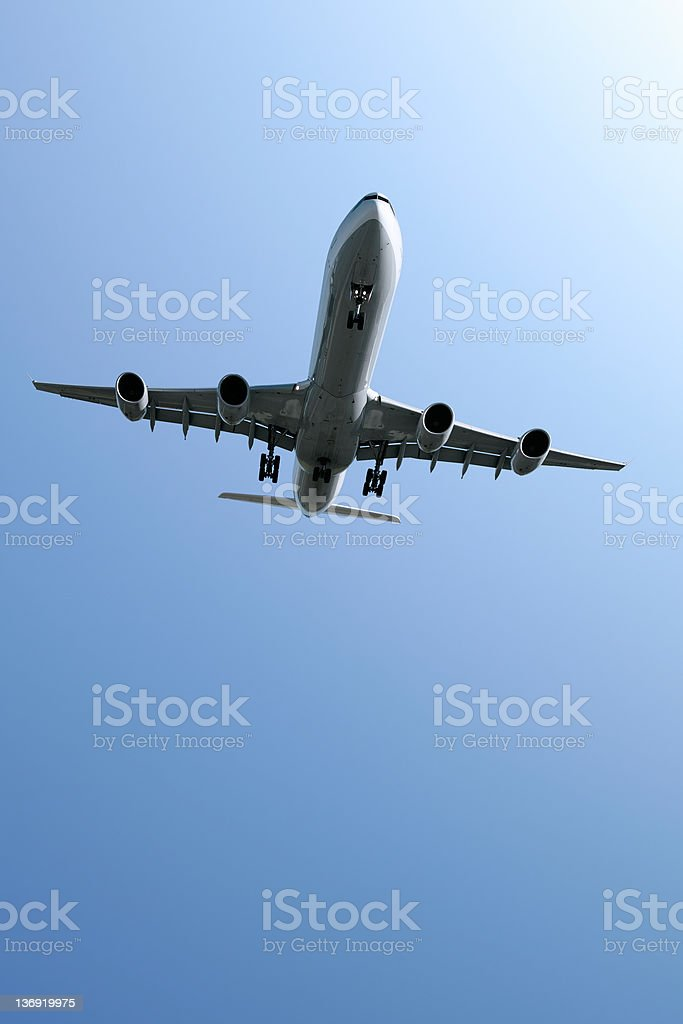 XL jet airplane landing in blue sky royalty-free stock photo