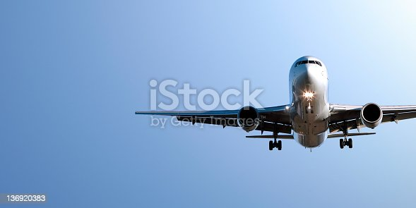 jet airplane in close-up landing in clear blue sky, panoramic frame