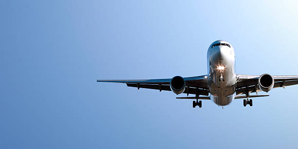 jet airplane landing in blue sky stock photo