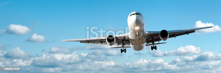 jet airplane landing in bright cloudy sky, panoramic frame