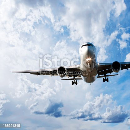 jet airplane in close-up landing in bright cloudy sky, square frame