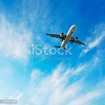 jet airplane landing in bright wispy sky, square frame (XL)