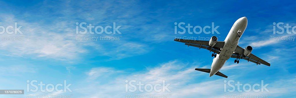 jet airplane landing in bright sky stock photo
