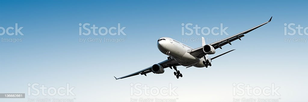 jet airplane landing in clear blue sky stock photo