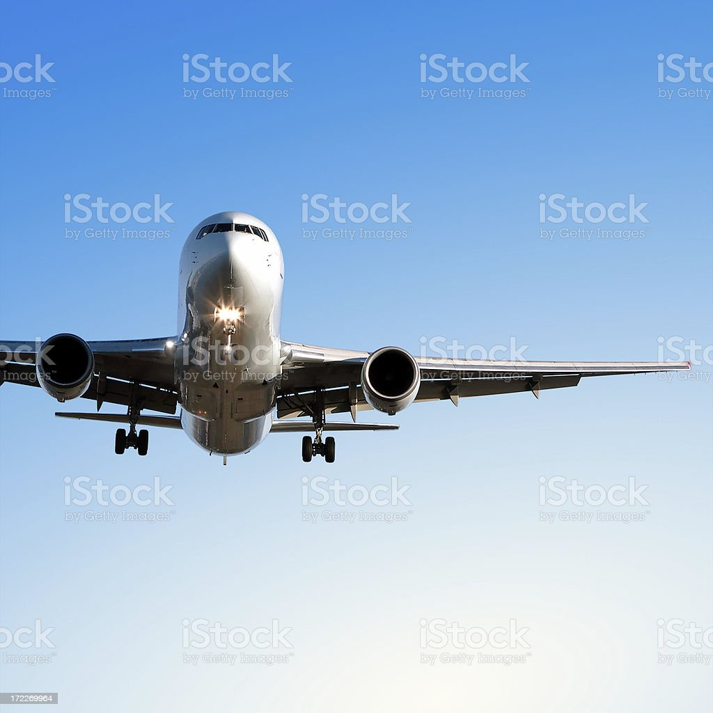 jet airplane landing in clear blue sky royalty-free stock photo