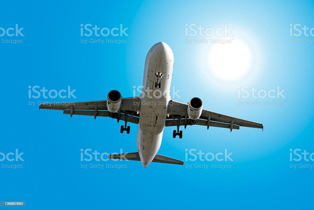 XXL jet airplane landing in sunny sky stock photo