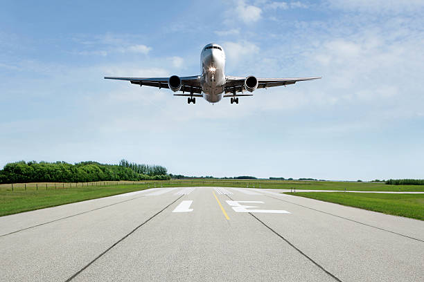 XL jet airplane landing on runway jet airplane landing on runway with bright sky (XL) airfield stock pictures, royalty-free photos & images