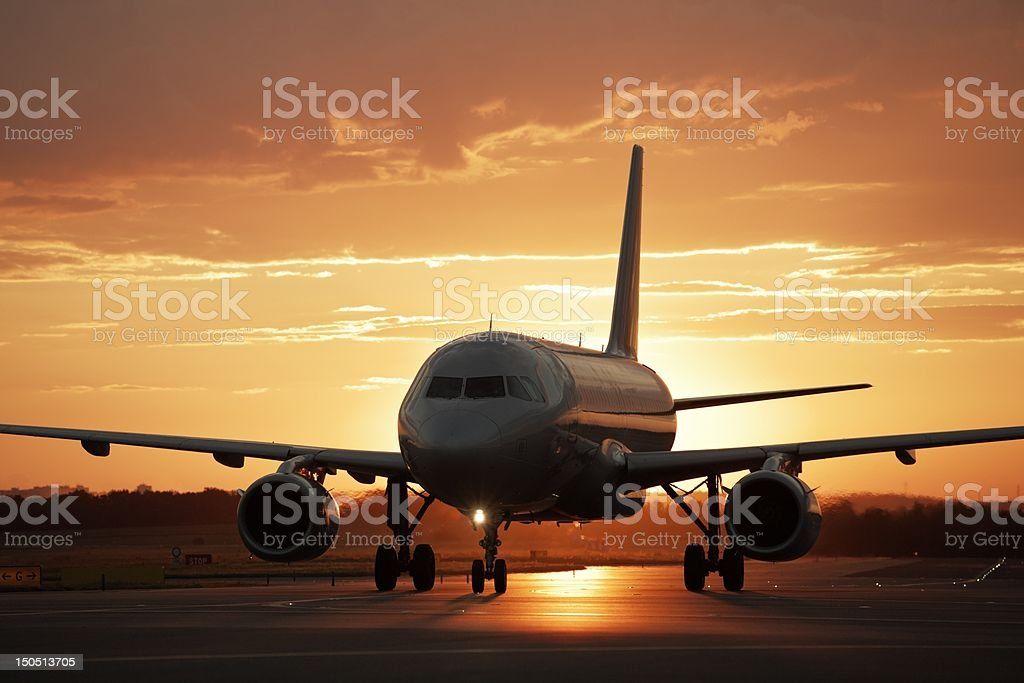 Jet airplane on runway at sunset stock photo