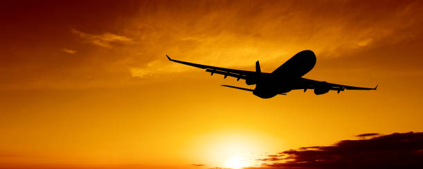 XL jet airplane taking off at sunset stock photo