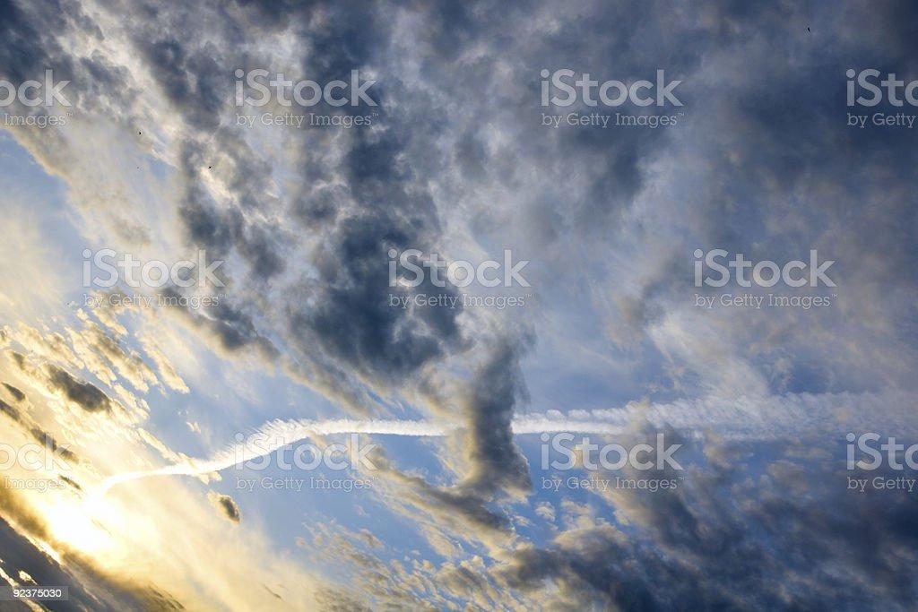Jet airplane trace across turbulent skies royalty-free stock photo