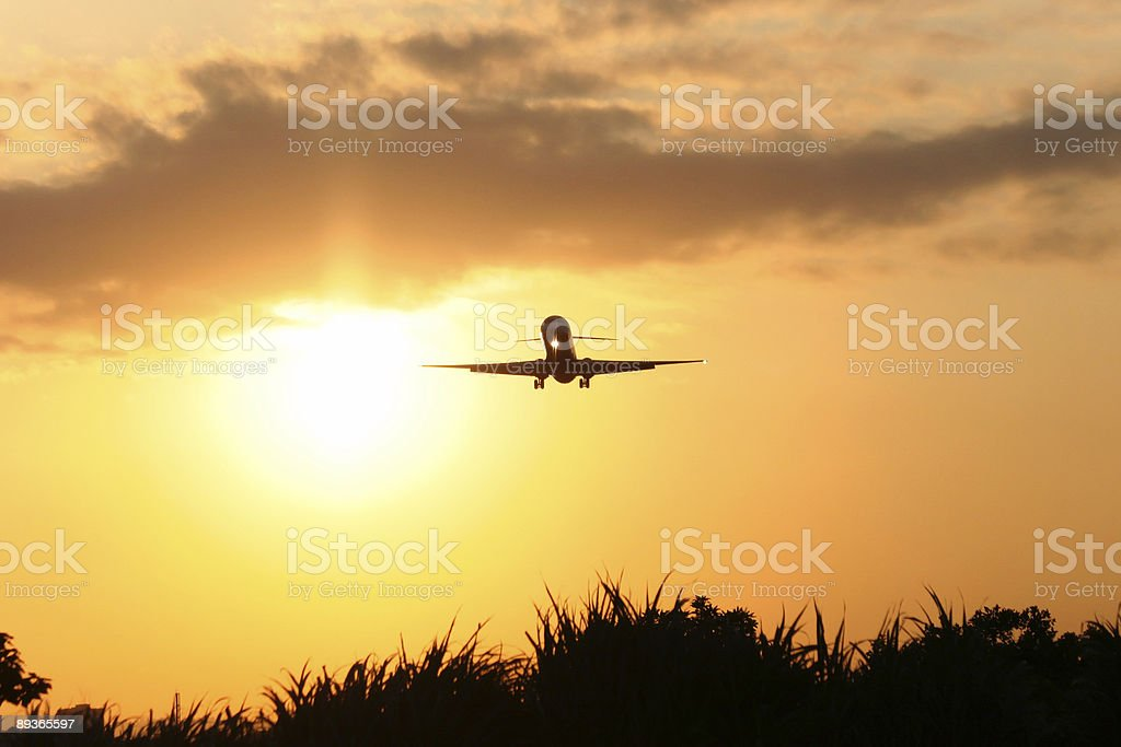 Jet Coming in for a landing at sunset royalty free stockfoto