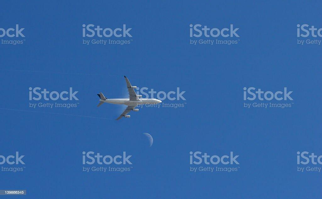 Jet crosses moon stock photo