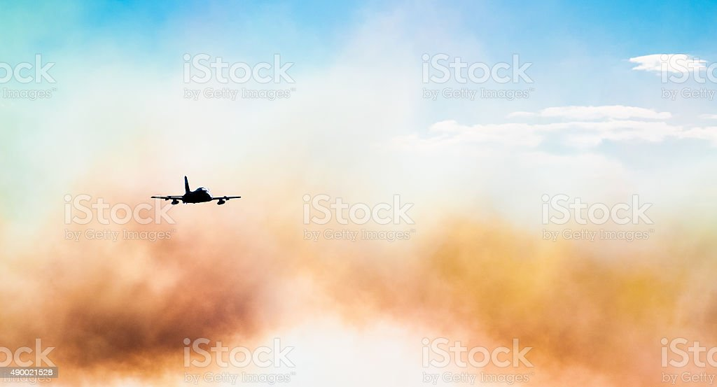 Jet fighter flying through  smoke stock photo