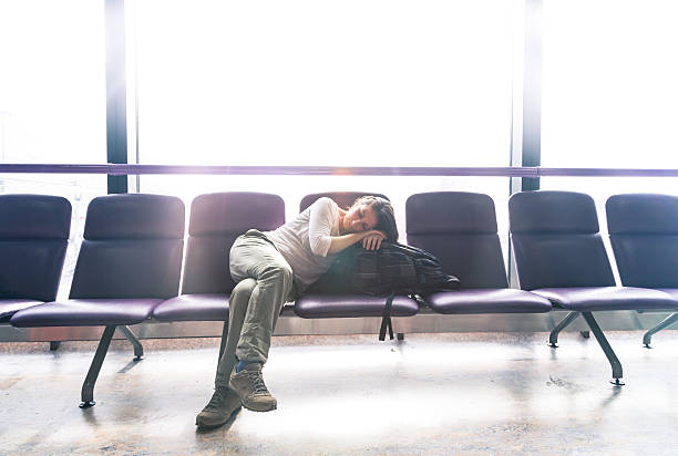 Jet lag Bored woman in a airport lounge is sleeping while waiting her delayed flight jet lag stock pictures, royalty-free photos & images