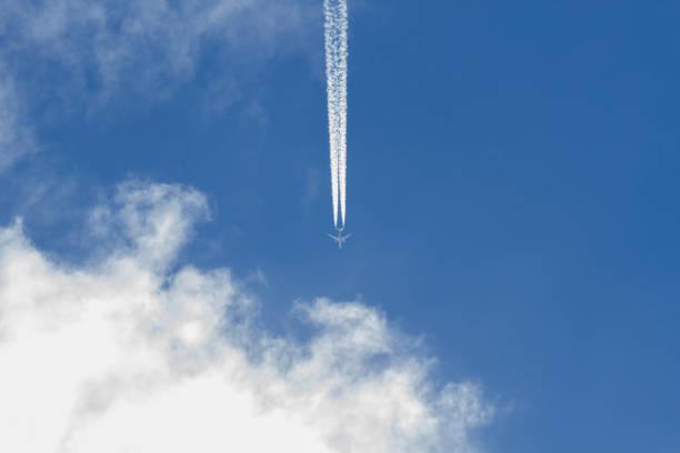 Jet leaving Trail in the Sky and Clouds - Avion dejando Rastro en el Cielo y nubes stock photo