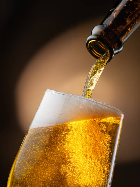 Jet of beer out of the bottle is poured into a beer glass, causing a lot of bubbles and foam. Dark brown background. stock photo