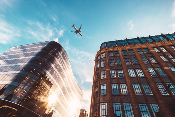 Jet plane aircraft traveling in the sky over the center of Glasgow city buildings. stock photo