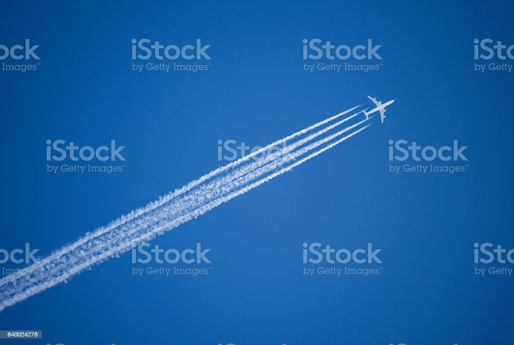 A jet plane flying overhead leaves four condensation trails against a vivid, blue sky. stock photo
