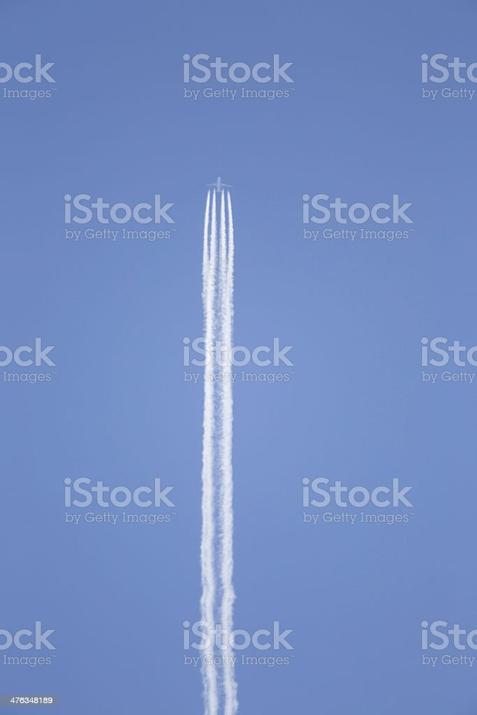 jet plane with trails in blue sky royalty-free stock photo