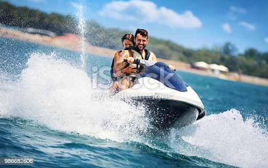 Closeup front view of a young couple riding a jet ski on a sunny summer day at open sea. The guy is driving and the girls is sitting behind.