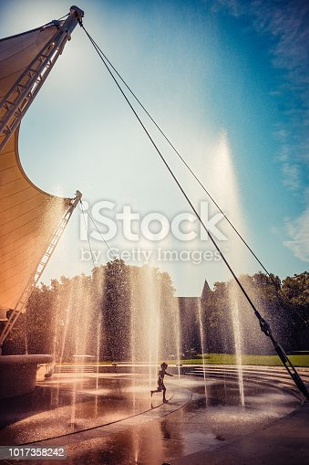 A young boy runs through a maze of fountain jets in Forsyth Park, Savannah.