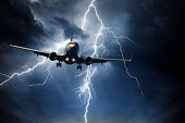 Passenger airplane travelling through sky against stormy bolt cloudscape