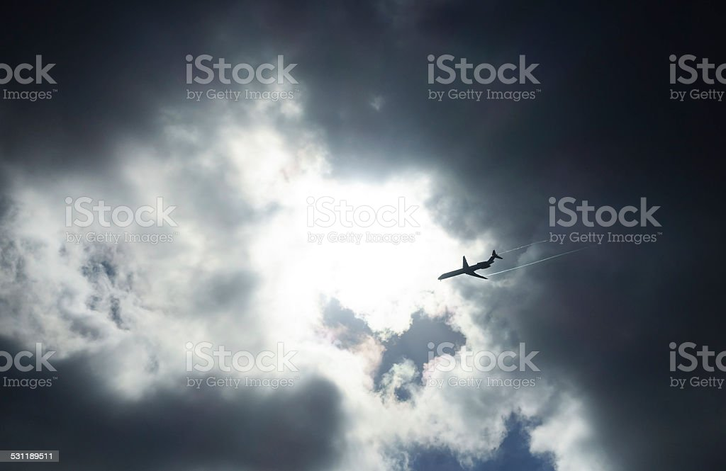 Jetliner aircraft flying under dark stormy clouds stock photo