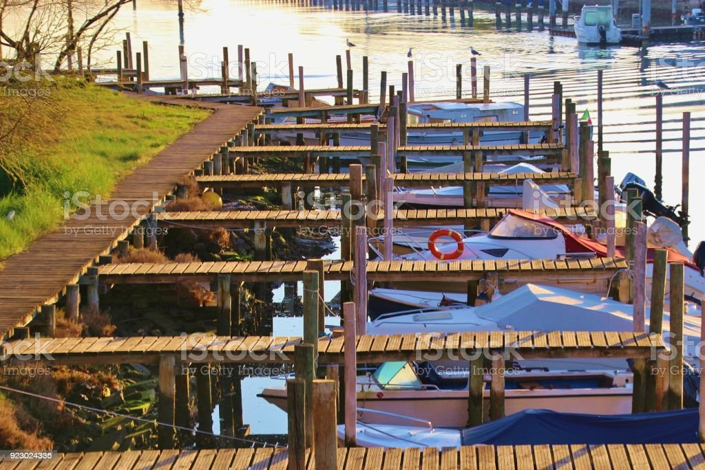 Jetties on the canal of Grado in bright morning light, Italy. stock photo