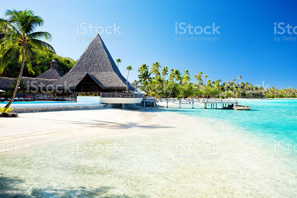 Jetty and boat on tropical beach with amazing water royalty-free stock photo