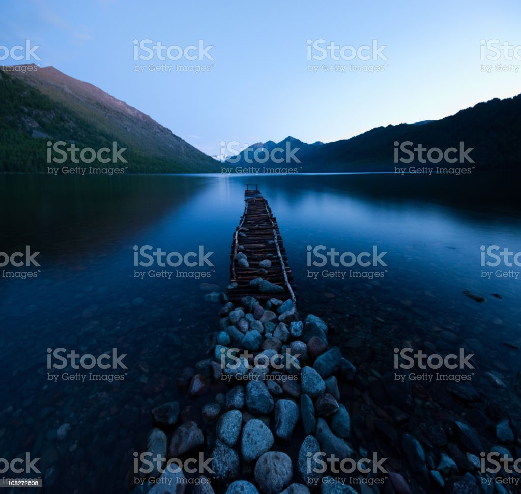 Jetty and stones on the shore of Multinskoe Lake royalty-free stock photo