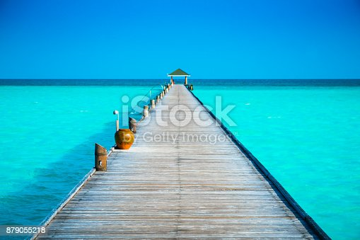 Jetty at tropical paradise beach at Dhiffushi Holiday island at South Ari atoll, Maldives. Beautiful turquoise Indian ocean sea with white sand. Luxury travel holidays background. Property released.