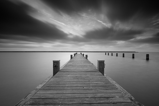 Jetty at lake Markermeer in black and white.