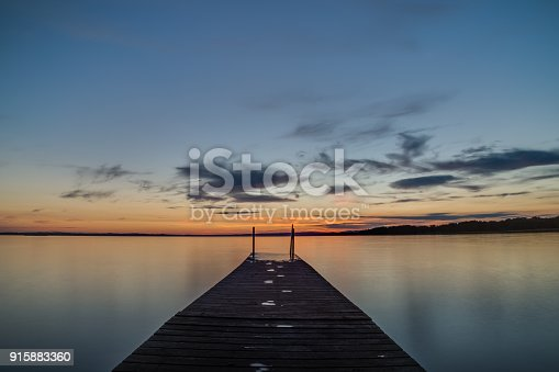 1088451256 istock photo Jetty at sunset with wet footprints 915883360