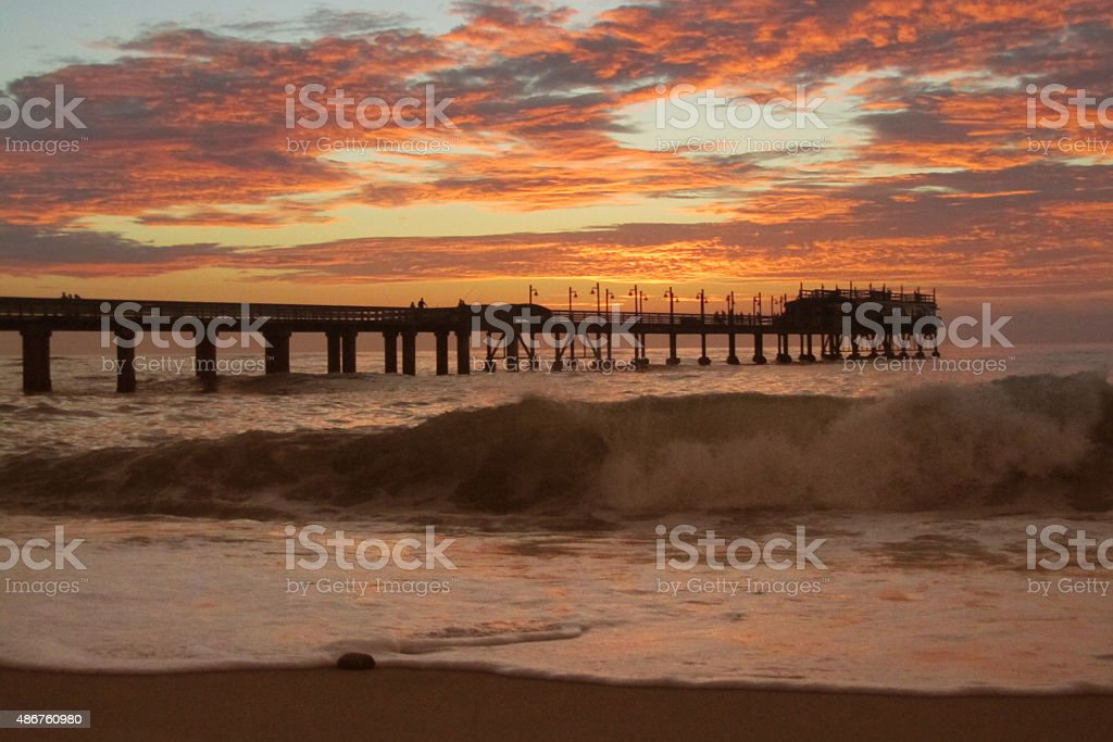 Jetty in Swakopmund during sunset. Jetty in Swakopmund, Namibia, during sunset. Seen from the beach. A wave is rolling towards the beach. 2015 Stock Photo