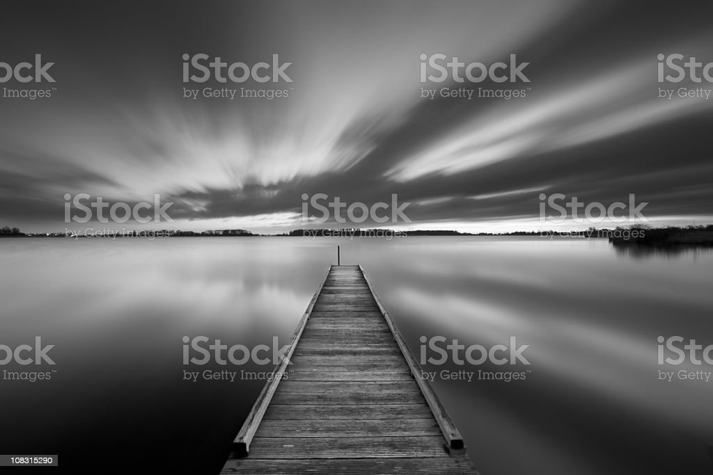 Jetty on a lake in black and white stock photo