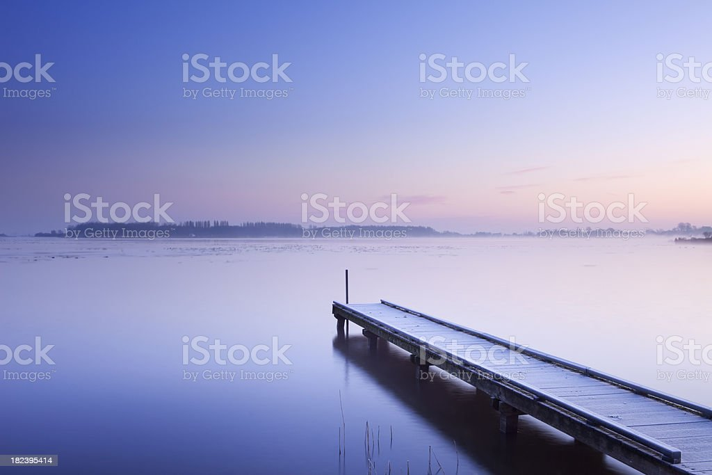 Jetty on a still lake in winter in The Netherlands royalty-free stock photo